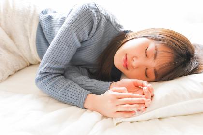 布団に入って睡眠を取る若い女性