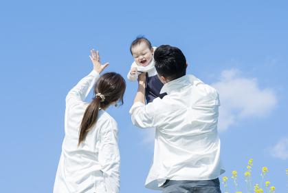 青空のもと、赤ちゃんを高く抱き上げる父母
