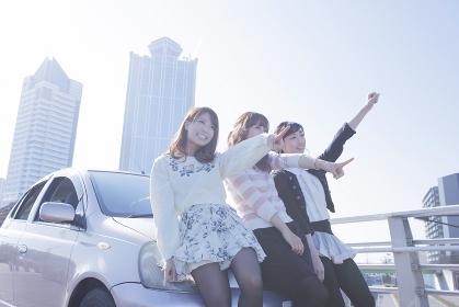 友達と車の前で楽しそうに指差す女性