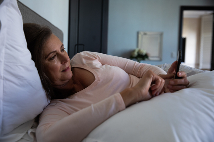 Caucasian woman enjoying time at home, social distancing and self isolation in quarantine lockdown, lying in bed, using a smartphone in bedroom.