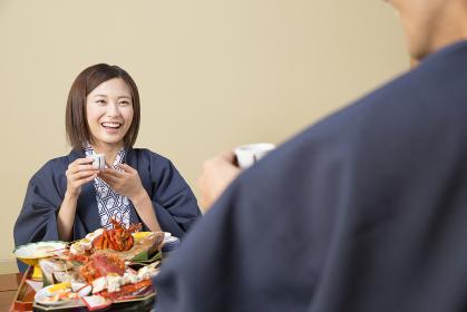 旅館で食事をするカップル