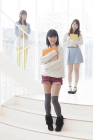 ノートを持って階段に立つ女子学生