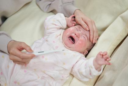 熱を出して泣くアジア人の赤ちゃん