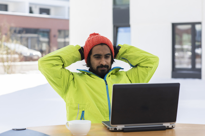 young man working with laptop outside in snow