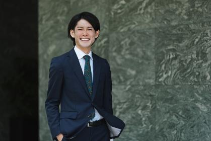 出社する若い男性・マンションのロビー背景・ビジネスイメージ