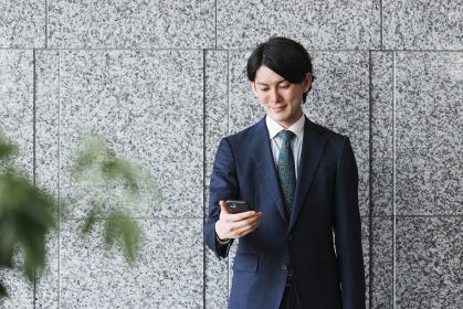 スマートフォンを持つ若い男性・IoTとビジネスのイメージ