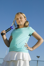 Young girl standing on tennis court Holding Tennis Racket portrait low angle view