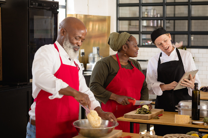 Side view of an Senior African American woman and man at a cookery class, listening to instructions from a Caucasian female chef wearing chefs whites and a black hat and apron, using a tablet computer while they work standing at a wooden table of ingredients