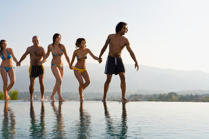 People walking by a pool, holding hands