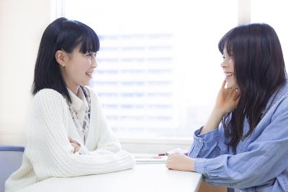 教室で友達と会話する女子学生