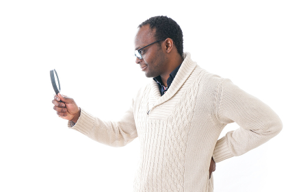 虫眼鏡を見る男性