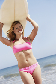 Woman Carrying Surfboard Over Head On Beach