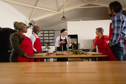 Side view of a multi-ethnic group of Senior adults at a cookery class, the diverse adult students listening to instructions from a Caucasian female chef wearing chefs whites and a black hat and apron, standing around a wooden table of ingredients wearing red aprons