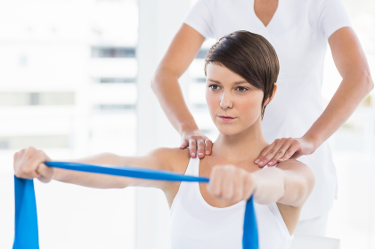Woman with trainer holding resistance band