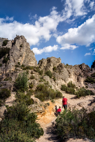 Father and daughter hike up cliff in summer in Mediterranean France