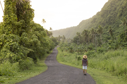 Man with sun hat and curly hair walking on empty road in tropical area