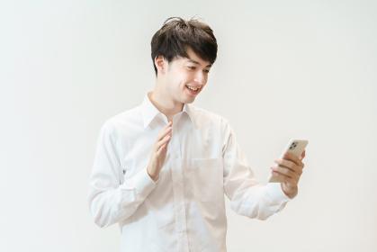 笑顔でスマートフォンに手を振る若い男性