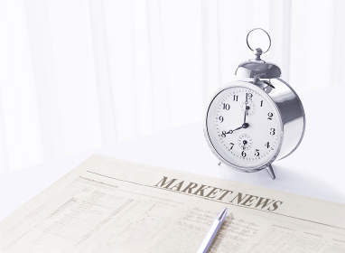 窓辺の目覚まし時計と新聞