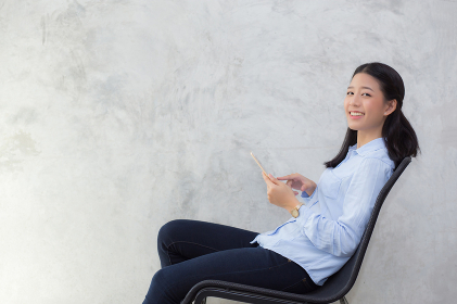 Beautiful young asian woman touching tablet computer and smile s