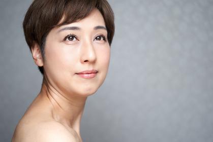 目線を外して微笑む中年の日本人女性