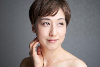 目線をそらして微笑む中年の日本人女性