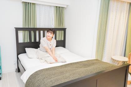 ベッドでリラックスをする若い女性