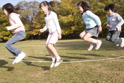 みんなで長縄跳びをする小学生たち