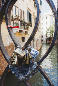 Padlocks attached to railings on bridge above venetian canal