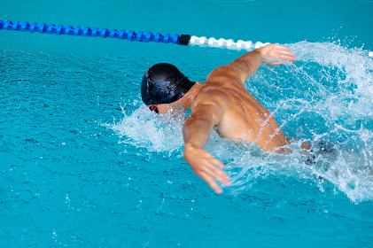 High angle side view of a Caucasian male swimmer at swimming pool, wearing a black swimming cap and goggles, splashing, swimming butterfly