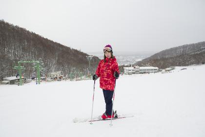 小雪舞うスキーゲレンデと女性スキーヤー