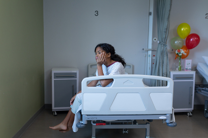 Bored sick mixed race girl sitting on hospital bed resting head on hand. medicine, health and healthcare services.