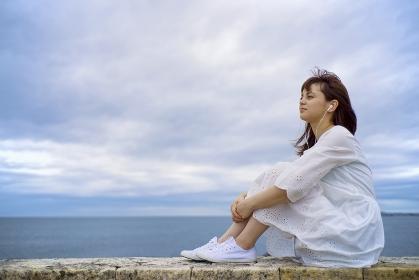 海岸に座って音楽を聴く日本人女性