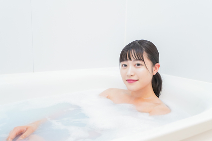 お風呂でお湯に浸かる若い女性