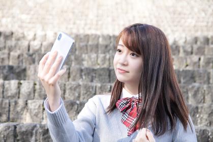 スマホで自撮りする女子高校生