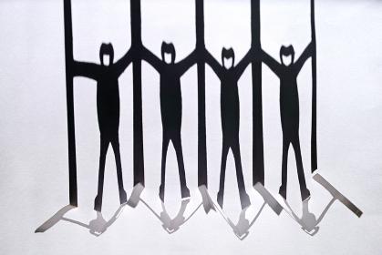 新型コロナ対策で衝立を挟んで繋がる人々の切り紙の影。白い背景。