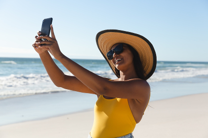 Smiling mixed race woman on beach holiday taking selfie. outdoor leisure vacation time by the sea.