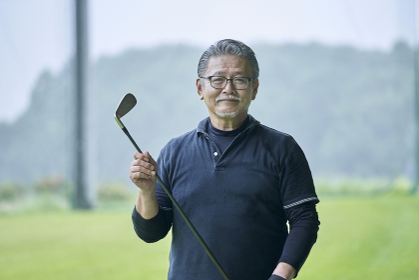 ゴルフ場で練習をするシニアの男性