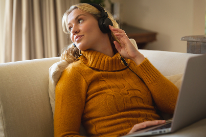 Smiling caucasian woman relaxing on couch in living room wearing headphones and using laptop. spending free time at home with technology.