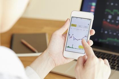 オンライン投資をする日本人の女性の手元
