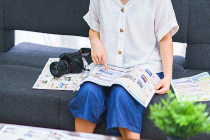 パンフを見ながら旅行の手配をする若い女性【goto travel キャンペーン】