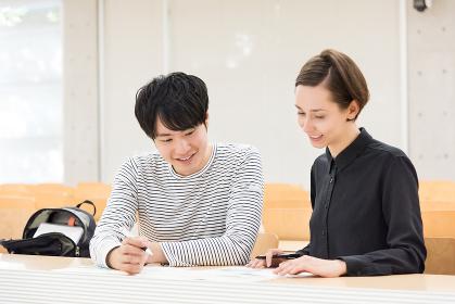 教室で勉強をする外国人の男女(国際化・留学イメージ)