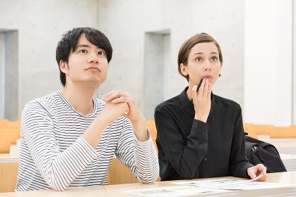 教室で講義を聞く外国人の男女(国際化・留学イメージ)