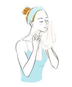 スキンケア タオルで顔を拭く女性