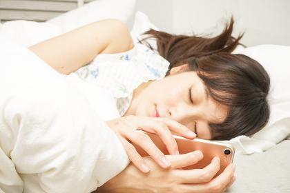 寝る前に携帯を使う若い女性