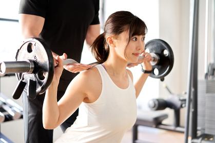 トレーナーの補助付きでバーベルスクワットをするアジア人女性