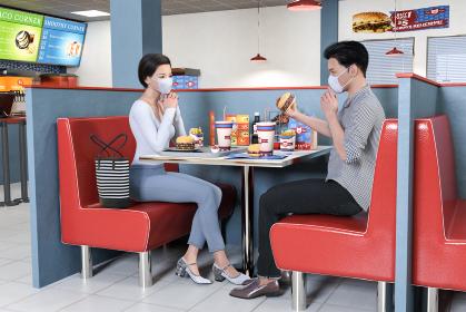 ファーストフード店でハンバーガーを店内で食べる男女
