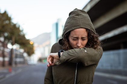 Caucasian woman out and about in the city streets during the day, wearing a smartwatch, standing and covering her face while coughing and sneezing during coronavirus covid 19 epidemic