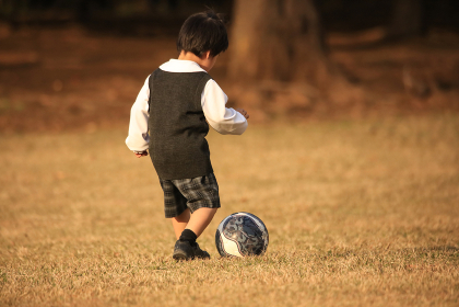 一人でサッカーボールを蹴って遊ぶ男の子