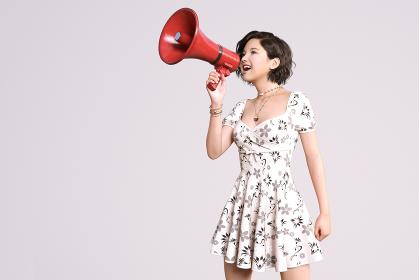 白いワンピースを着たウェーブのショートヘアの女の子が赤い拡声器を持ち発信するように叫んでいる