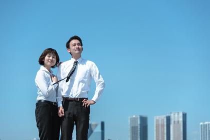 腰に手を当ててポーズをとる男性と女性(ビジネスイメージ)